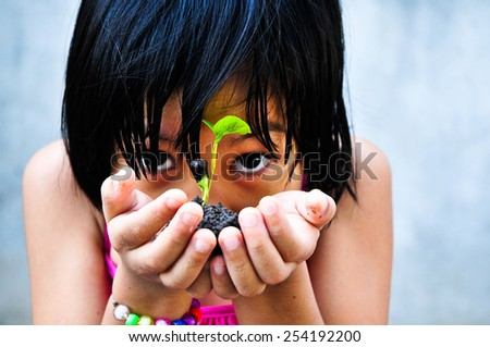 Asia girl were little planted in pots , Focus on little plant. - stock photo