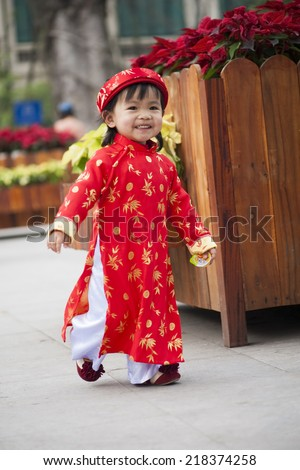 Asia little girl wears Vietnamese traditional long dress ( Ao Dai in Vietnamese) playing on playground by Dinh Tien Hoang street, Hanoi
