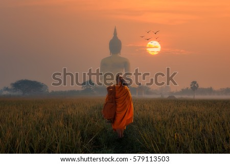 Asia Monk walking dhutanga behind Big Buddha at Wat Muang Angthong, Temple thailand in sunset.