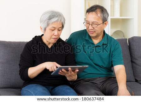 Asia old couple using tablet - stock photo