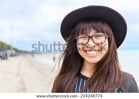 asia teenage girl with eyeglasses and hat with blur beach background - stock photo