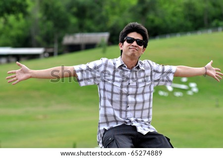 Asia Thailand Man Sunglasses Extend The Arms - stock photo