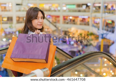 asia woman carrying paper shopping bags on escalator of shopping mall and bokeh light background. (vintage color tone)