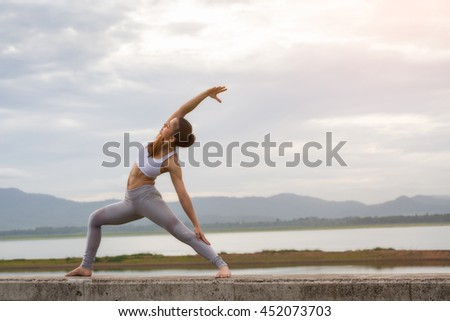 Asia woman doing yoga fitness exercise for relax and healthy at lake in morning, Nature background, Concept outdoor sport and health