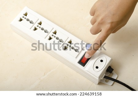 asia woman hand turn on switch multiple  socket plug electric - stock photo