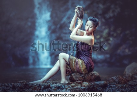 Asia woman is bathing at the waterfall happily.