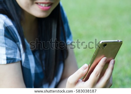 Asia woman relax sit on grass use smart phone with copy space.
