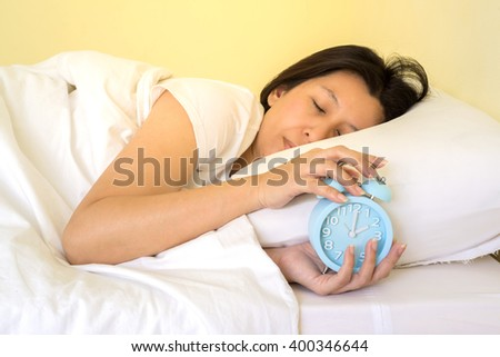 asia woman turns off the alarm clock waking up in the morning from a call.  - stock photo