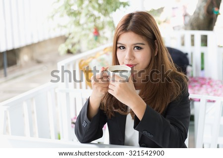 Asia young business woman sitting and drinking hot coffee in cafe, business concept