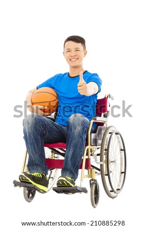 asia young man sitting on a wheelchair and thumb up with a basketball - stock photo