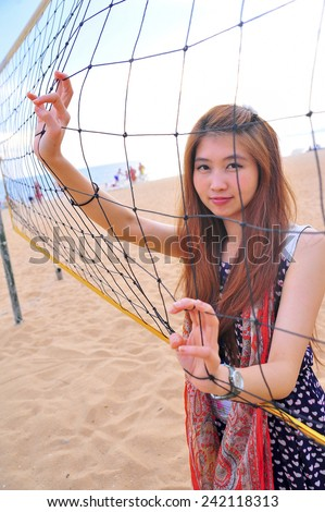 Asia young woman behind Volleyball net at the beach, sport concept