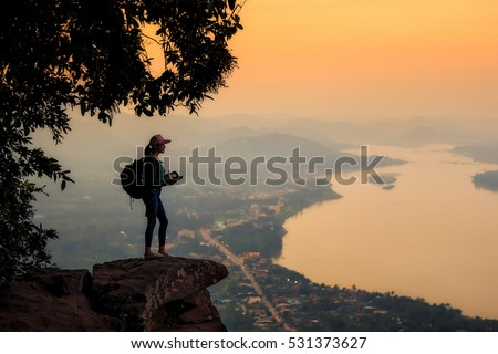 Asia young woman hiking a mountain alone in his travels happily.