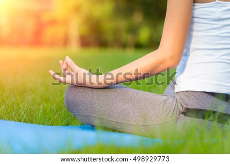 Asia young woman practicing yoga in the park and sport yoga.