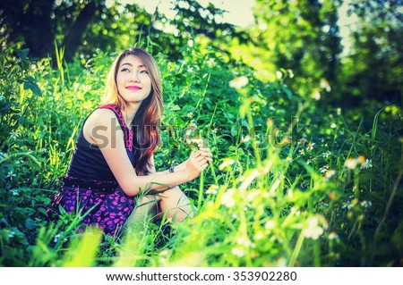 asia young woman wearing modern dress with grass flowers on sunny day, vintage effect
