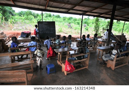 ASIAFO AMANFRO, EASTERN, GHANA - NOVEMBER 14: Students attending class in an outdoors elementary school classroom in the Yilo Krobo District near Accra, Ghana on November 14, 2011. Mud brick building. - stock photo