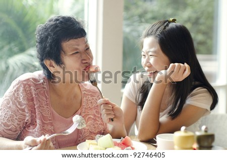 Asian adult daughter feeding fruit to senior mother - stock photo