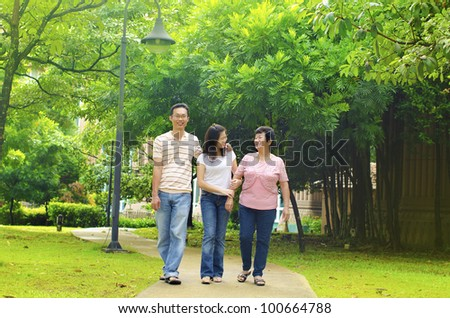 Asian adult having a outdoor walk with senior mother - stock photo