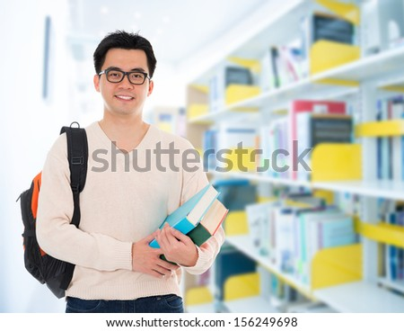 Asian adult student in casual wear with school bag carrying text books standing inside school library building. - stock photo