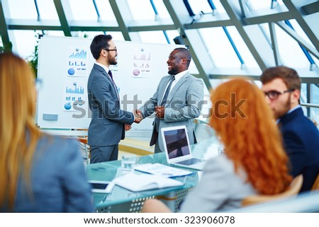Asian and African businessmen handshaking after signing contract - stock photo