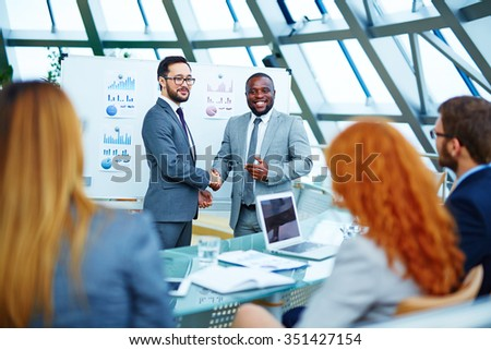 Asian and African businessmen handshaking and looking at employees in office - stock photo