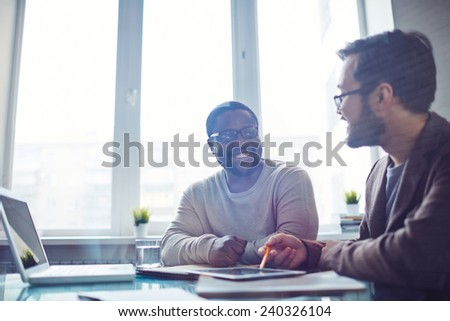 Asian and African employees discussing ideas in office - stock photo