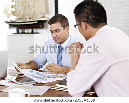 asian and caucasian business executives reviewing and discussing business performance in office of a multinational company. - stock photo
