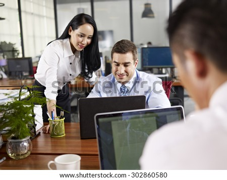 asian and caucasian business people working together in office of a multinational company. - stock photo