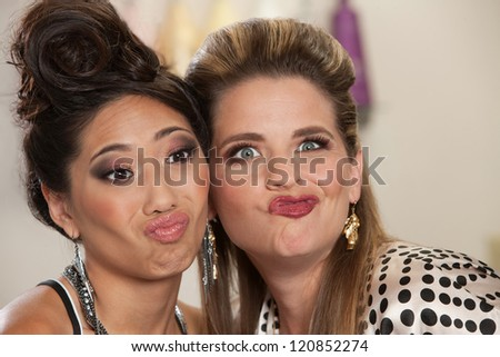 Asian and European pair of women making faces - stock photo