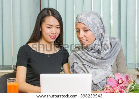Asian and muslim girls working together on a laptop