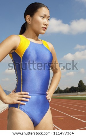 Asian athlete woman in sportswear with hands on hips standing on racetrack - stock photo