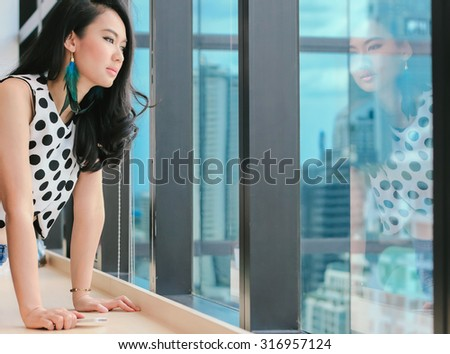 Asian attractive woman thinking and looking out window - stock photo