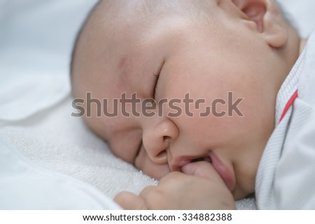 Asian babies sleep on white linen.