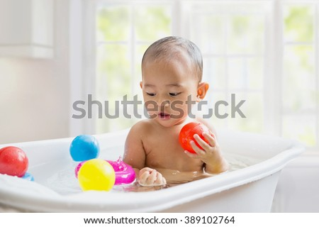 Asian baby bathing in the white bathtub. smiling and playing with her toy - stock photo