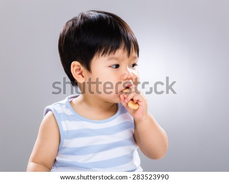 Asian baby boy eat with his finger food - stock photo