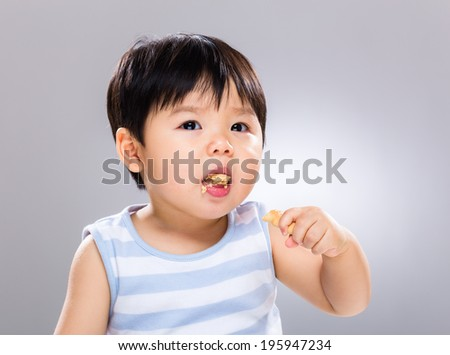 Asian baby boy eating biscuit - stock photo