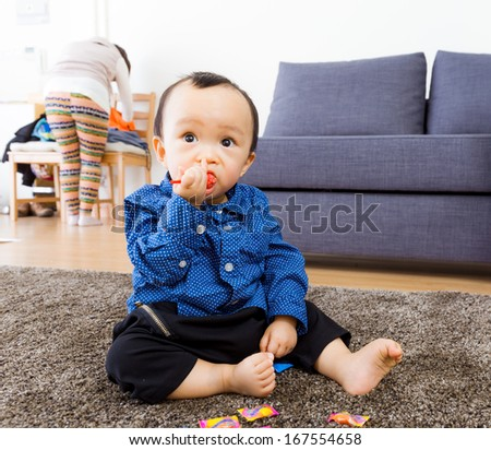 Asian baby boy eating candy - stock photo
