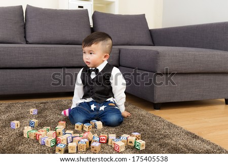 Asian baby boy play wooden block at home - stock photo