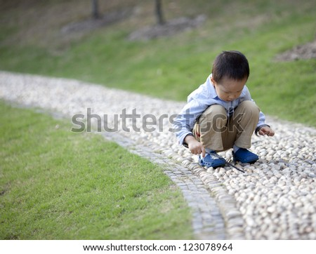 Asian baby boy playing in the park with a stick