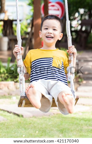 Asian baby boy playing on a swing and having fun in park - stock photo