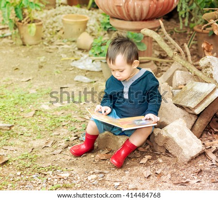 Asian baby boy reading tale book , Boy wear red boot sitting on a log