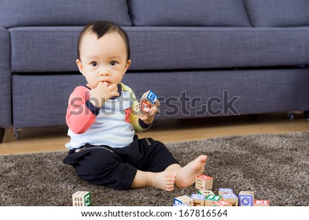 Asian baby boy with finger in mouth - stock photo