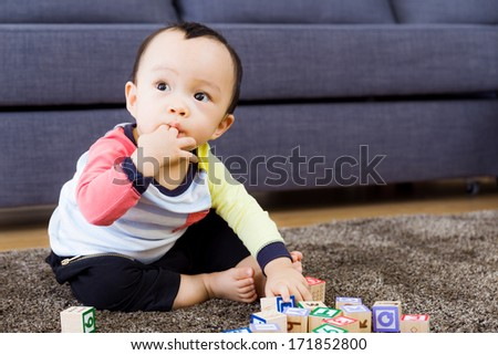 Asian baby boy with fingers in mouth at living room - stock photo