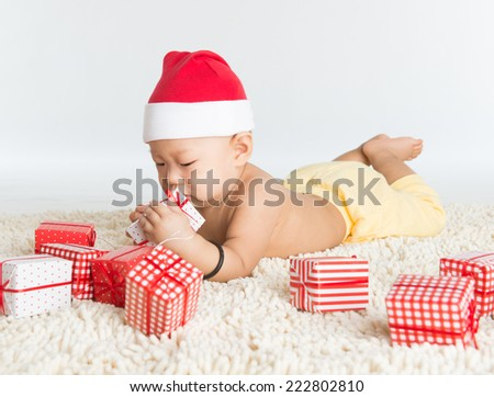 Asian baby boy with santa hat playing with Christmas present on floor. - stock photo