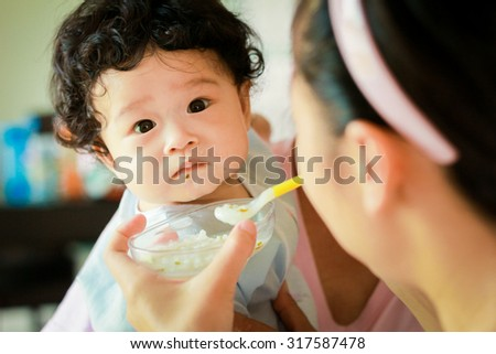 Asian baby children girl with curly hair feeding