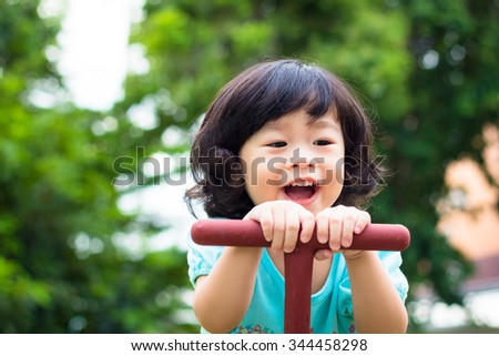Asian baby cute girl with curly hair in the playground - stock photo