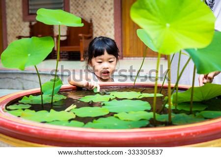 Asian baby cute girl with curly hair play lotus sink