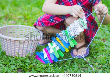 Asian baby cute girl with curly hair play the clothes peg