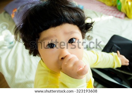 Asian baby cute girl with curly hair suck finger