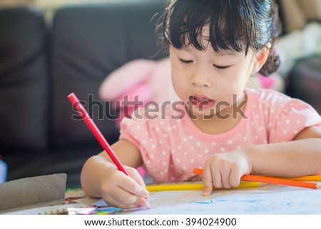 Asian baby cute girl with curly hair write a paper - stock photo