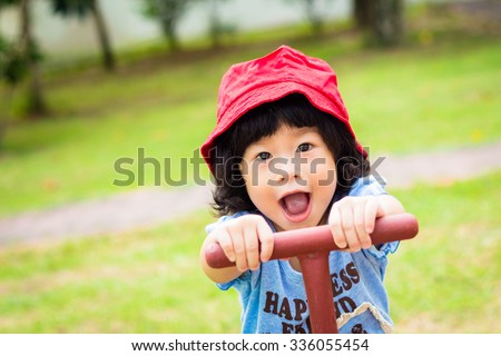 Asian baby cute girl with red hat in the playground - stock photo